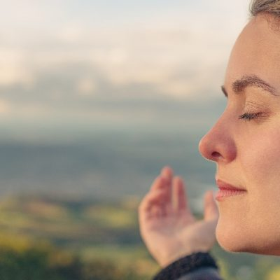 Image of the profile of a woman standing outside by mountains with her eyes closed and her arms outstretched.