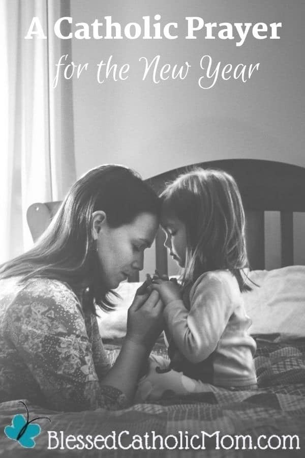 Image in black and white of a mother and her little daughter with their eyes closed holding hands and praying together while the mother is kneeling on the floor and the daughter is sitting on a bed. Words above the image read In A Catholic Prayer for the New Year.