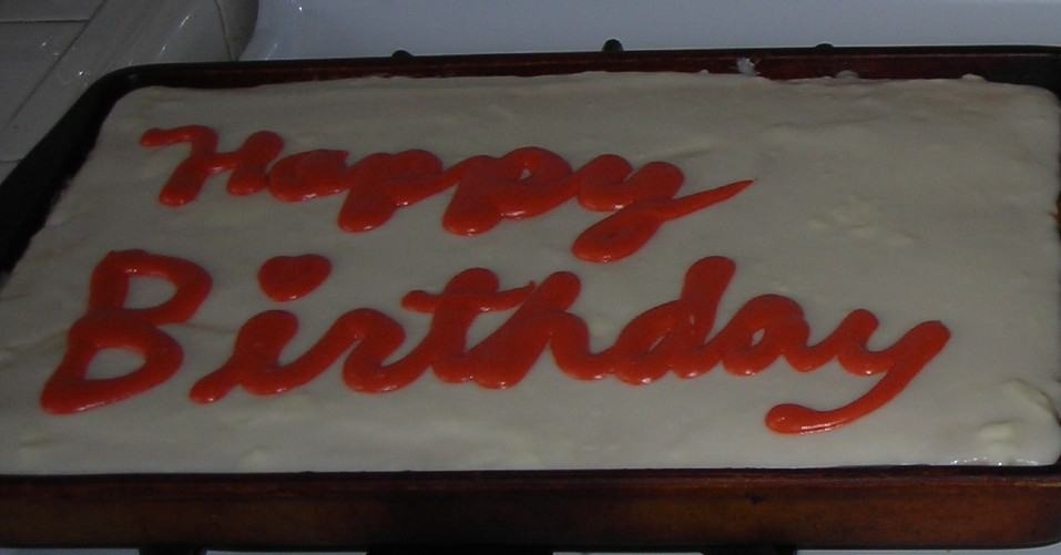 Image of a cake frosted in white with words in pink frosting reading Happy Birthday.