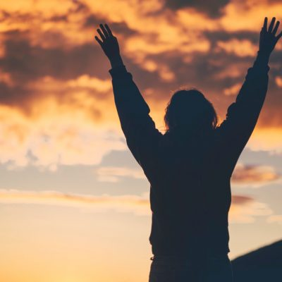 Image of the silhouette of a woman with her arms raised up in praise facing a sunset over a mountain.