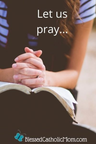 Image of a young woman sitting down on the ground with her hands clasped together on to of an open Bible.