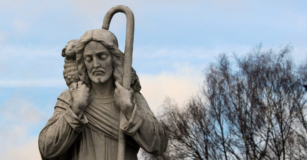 Image of a statue of Jesus the Good Shepherd holding a shepherd's staff in one hand and holding a lamb across His shoulders.