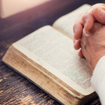 Image of a Bible open on a table by a window and the hands of a woman are clasped together on top of the Bible.
