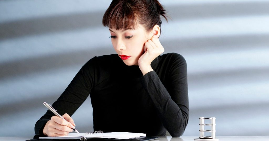 Image of a woman wearing a black shirt and red lipstick sitting at a table writing in her planner.