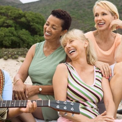 Image of four women sitting outside in a mountain area singing together while one of them plays the guitar.