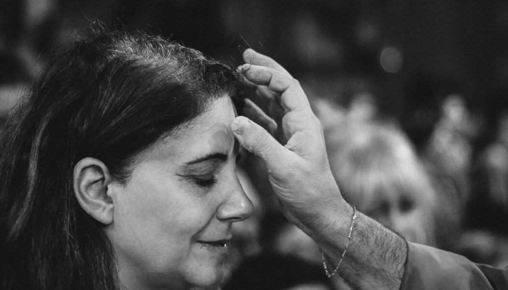 Image of a woman receiving ashes on her forehead on Ash Wednesday.