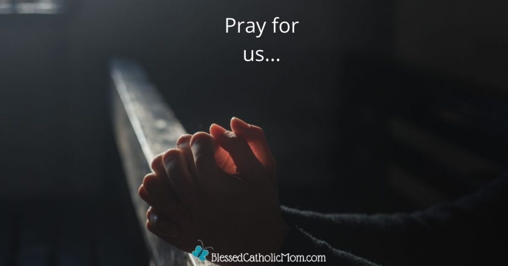 Image of two hands folded in prayer on the back of a pew in church. Words at the top of the image read: Pray for us... On the bottom of the image is the Bessed Catholic Mom logo.