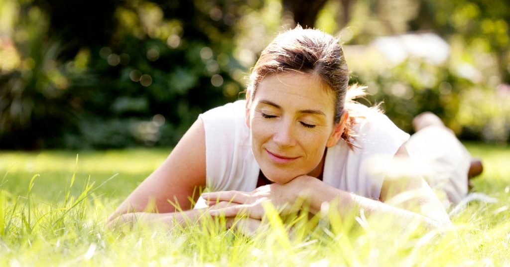 Image of a with her brown hair back in a ponytail and wearing a white shirt laying on her stomach on the grass with her chin resting on her hands, her eyes closed, and a smile on her face.
