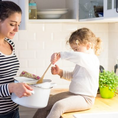Image of a mom holding a pot of something out to her little daughter who is sitting on the counter and mixing it.