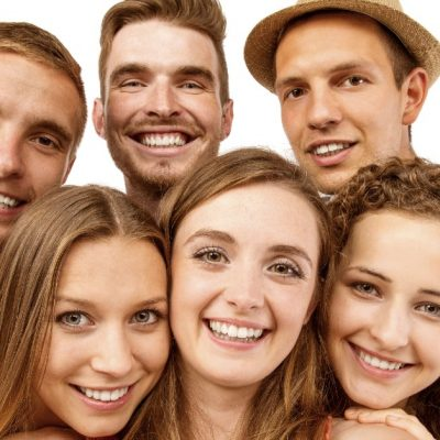 Image of six teens-three boys and three girls, standing together as one takes a selfie photo of them all.