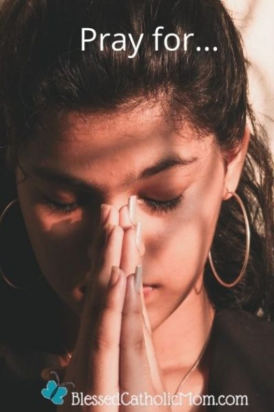 Image of a young woman with her hands folded in prayer in front of her face, hed bowed slightly, and eyes closed. The words Pray for... are at the top of the image and the logo for Blessed Catholic Mom is at the bottom.