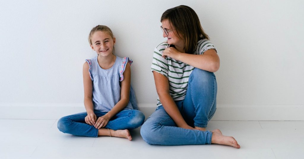 Image of a mom and daughter sitting together on the floor.