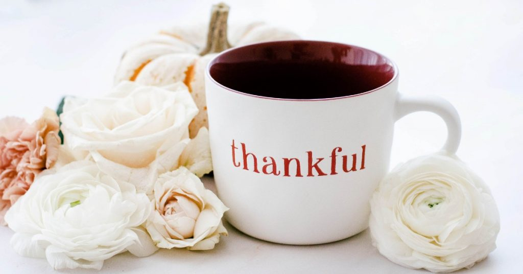 Image of a white mug with the word thankful on it surrounded by white, cream and a soft pink flower.