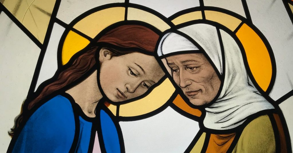 Image of a stained glass window showing the Visitation of the Blessed Virgin Mary to her cousin Elizabeth. The women are facing each other, holding each other's arms and each bowing their head to the other.