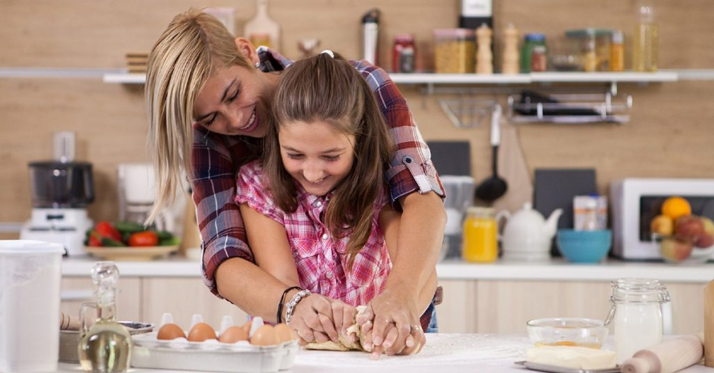 Image of a mom and her daughter in the kitchen making pasta together as the mom stands behind her daughter and they are forming the pasta with their hands in the dough.