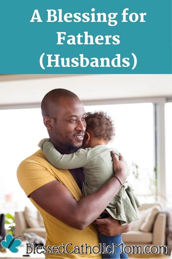Image of a father at home with his cute little daughter holding her in his arms and she is hugging him back. Words above the image read: A Blessing for Fathers (Husbands). The logo for Blessed Catholic Mom is below the image.
