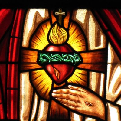 Image of a stained glass window of Jesus with a halo, His right hand raised as if in blessing and his left hand under His Sacred Heart.