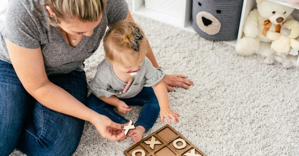 Image of a mom and toddler daughter sitting on the carpet at home playing a game of tic tac toe on a wooden game board.