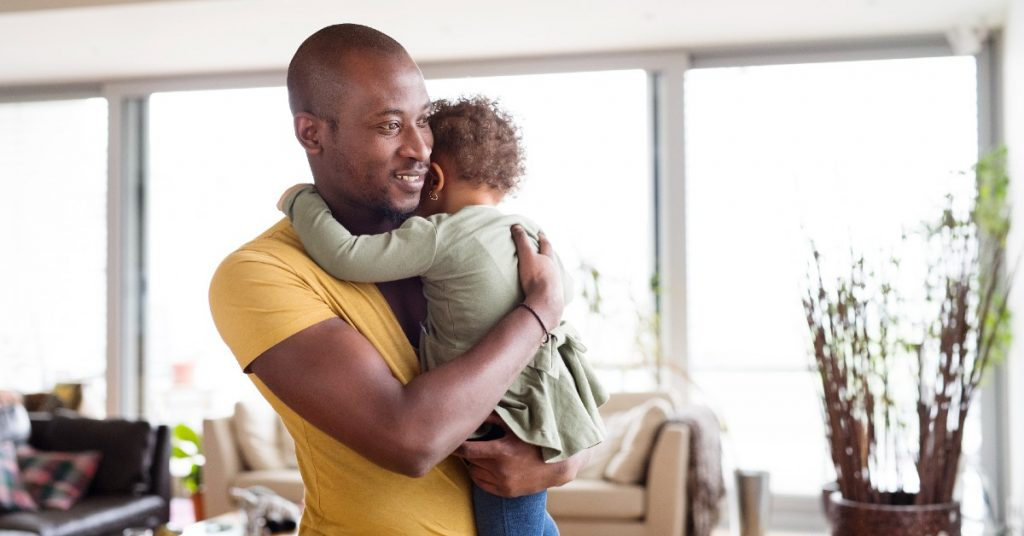 Image of a father at home with his cute little daughter holding her in his arms and she is hugging him back.