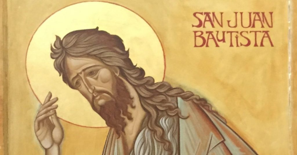 Image of an icon of St. John the Baptist: He has long brown hair, a beard, a halo around his head and is standing, holding up his right hand.