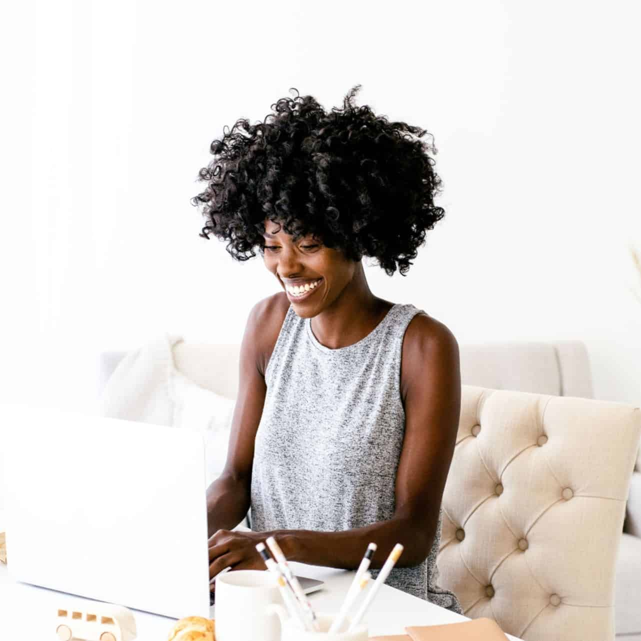 Image of a woman smiling as she uses her computer.