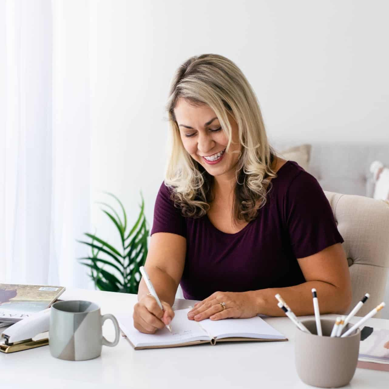 Image of a woman smiling as she sits at a desk and writes on a pad of paper.