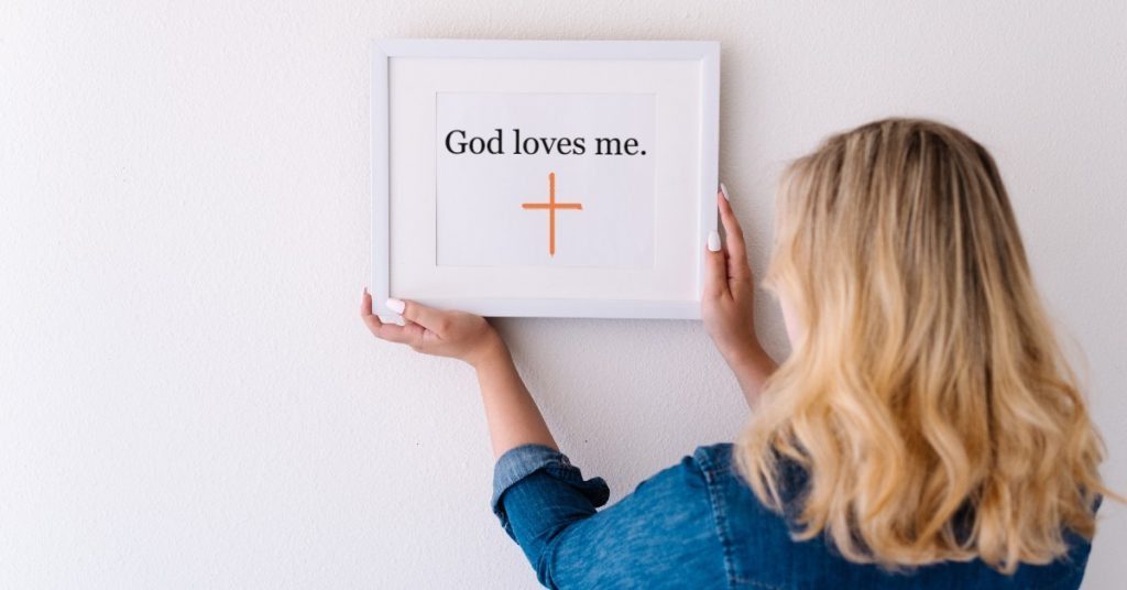 Image of a woman with blond hair wearing a blue shirt with her back to the camera hanging a framed quote that reads God loves me and has an orange cross on it.