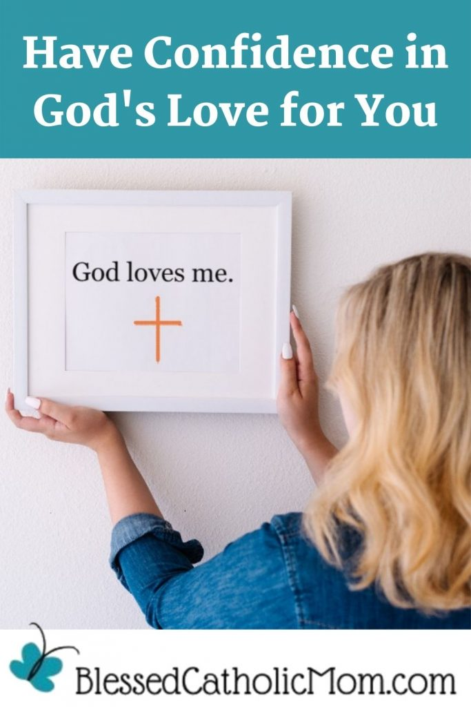 Image of a woman with blond hair wearing a blue shirt with her back to the camera hanging a framed quote that reads God loves me and has an orange cross on it. Words above the image read Have Confidence in God's Love for You. Logo below the image is Blessed Catholic Mom dot com.