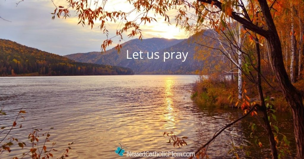 Image of the sun shine on a lake with mountains in the background and part of a fall tree in the foreground on the right side. The words Let us Pray are imposed over the mountains and the logo for Blessed Catholic Mom is at the bottom of the image.