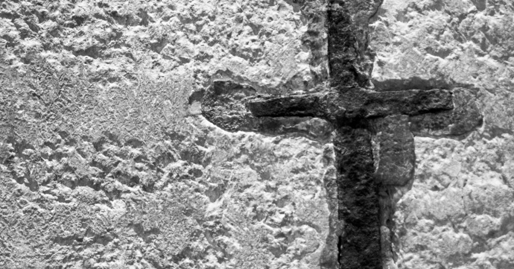 Image in black and white of a concrete wall with a cross etched in the wall that is darker than the wall.