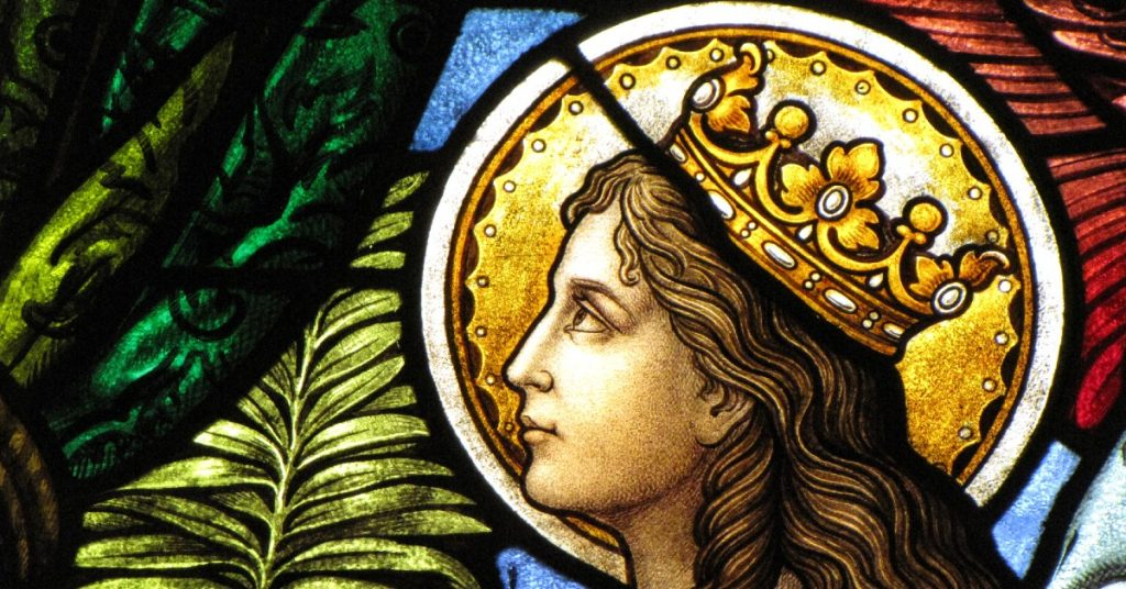 Image of a stained glass window of a female Christian martyr with a golden crown on and a golden halo behind her head.